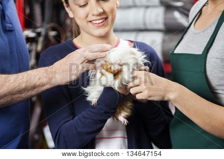 Girl Holding Guinea Pig With Father And Saleswoman