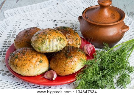 Plate with buns, clay pot and a sprig of dill on a white tablecloth on a light wooden background.