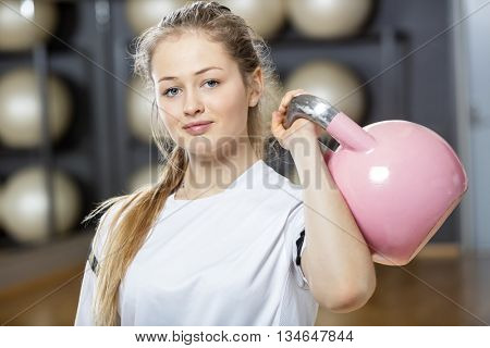 Attractive Young Woman Lifting Kettlebell In Gym