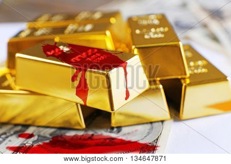 Gold bars with dollar banknotes and blood splashes