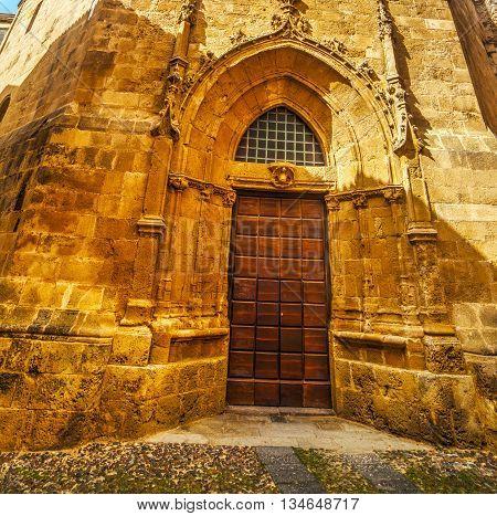 wooden door in Duomo steeple in Alghero Italy