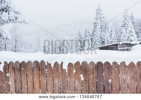 Rural winter scene. Snow covered wooden fence and snowy trees on background