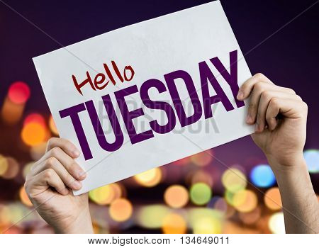 Hello Tuesday placard with night lights on background