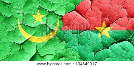 Mauritania flag with Burkina Faso flag on a grunge cracked wall