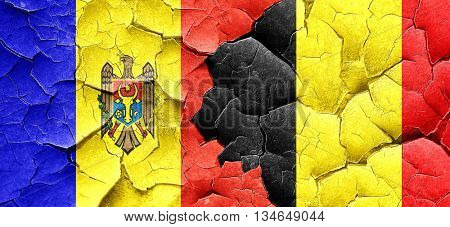 Moldova flag with Belgium flag on a grunge cracked wall
