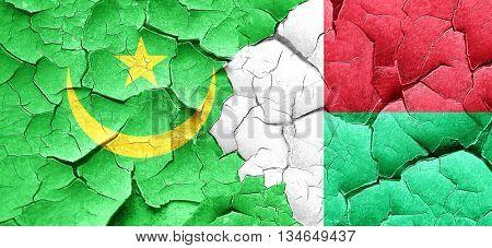 Mauritania flag with Madagascar flag on a grunge cracked wall