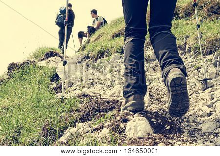 Closeup of trekking shoes. Person ascending a rocky road.