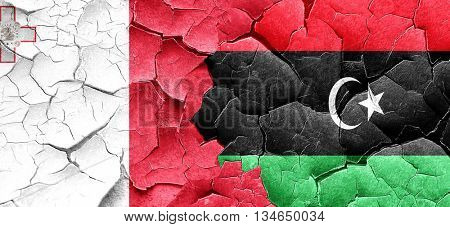 Malta flag with Libya flag on a grunge cracked wall