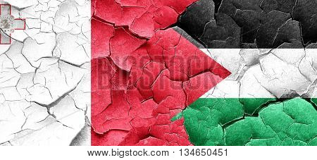 Malta flag with Palestine flag on a grunge cracked wall
