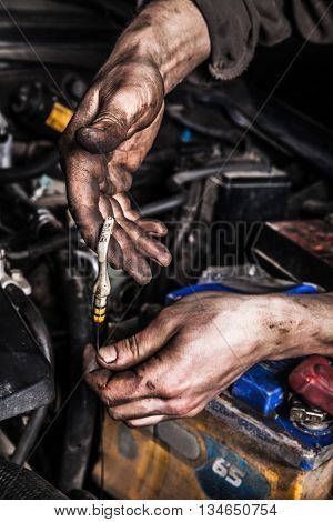 Dirty man hands with oil gage and battery