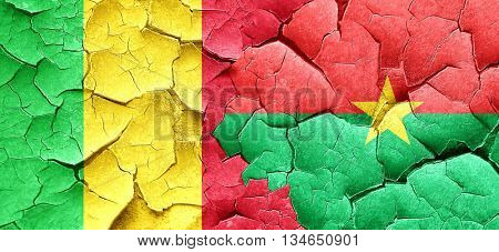 Mali flag with Burkina Faso flag on a grunge cracked wall