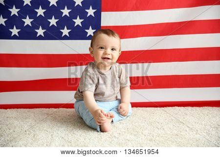 Adorable baby boy on American flag background