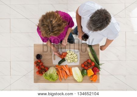High Angle View Of Wife Preparing Food While Her Husband Holding Glass Of Wine