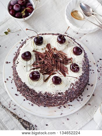 Black forest cake decorated with whipped cream and cherries Pie dark chocolate and cherry dessert on a white plate