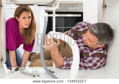 Woman Looking At Mature Male Plumber Fixing Sink Pipe