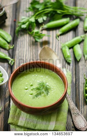 Fresh green pea soup with pea seeds and pea pods . Cream soup of green peas. A delicious lunch in a rustic style