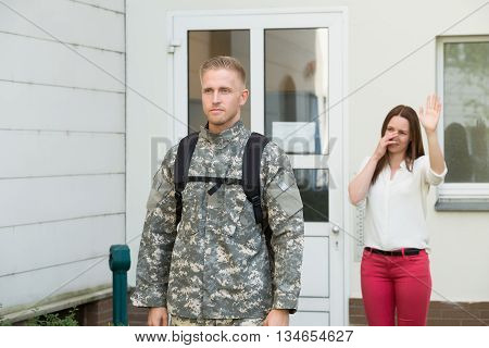 Unhappy Young Wife Waving Goodbye To Male Soldier Outside House
