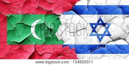 Maldives flag with Israel flag on a grunge cracked wall