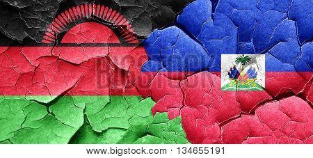 Malawi flag with Haiti flag on a grunge cracked wall