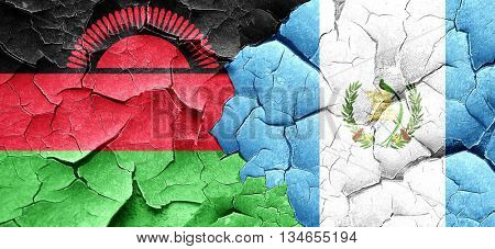 Malawi flag with Guatemala flag on a grunge cracked wall