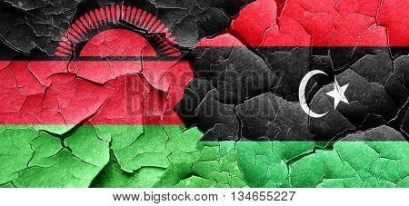 Malawi flag with Libya flag on a grunge cracked wall