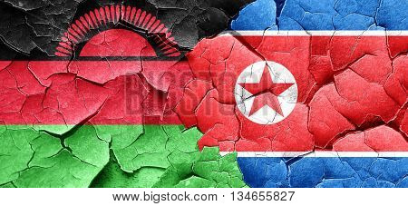 Malawi flag with North Korea flag on a grunge cracked wall