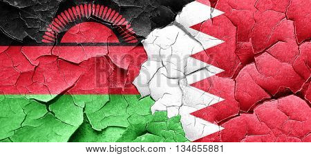 Malawi flag with Bahrain flag on a grunge cracked wall