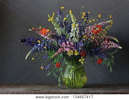 Summer still life with a bouquet of lupine and buttercups in a glass vase on a dark background.