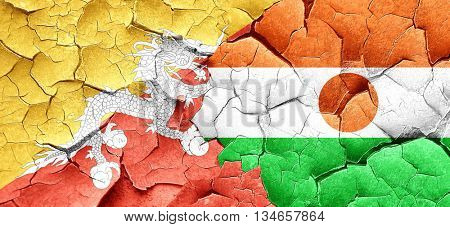 Bhutan flag with Niger flag on a grunge cracked wall