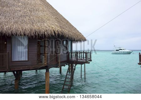 water bungalows and the boat in the ocean on the Maldivian island