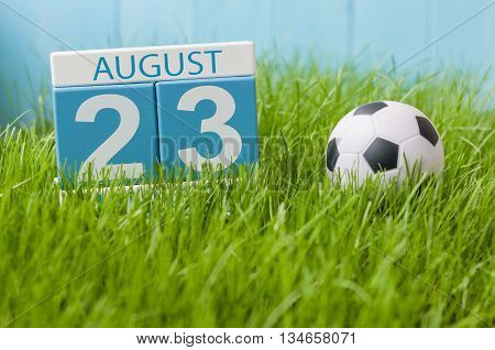 August 23rd. Image of august 23 wooden color calendar on green grass lawn background with soccer ball. Summer day. Empty space for text.
