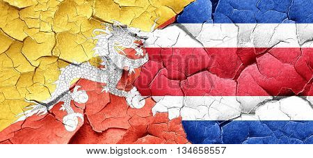 Bhutan flag with Costa Rica flag on a grunge cracked wall
