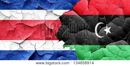 Costa Rica flag with Libya flag on a grunge cracked wall