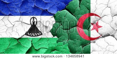 Lesotho flag with Algeria flag on a grunge cracked wall