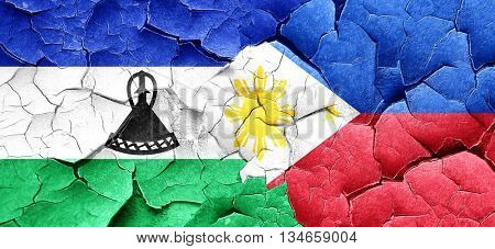 Lesotho flag with Philippines flag on a grunge cracked wall