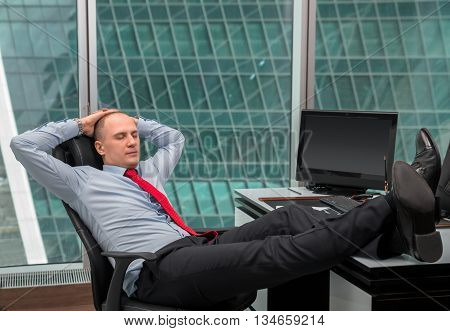 businessman relaxing at the office with his shoes on the desk inside office building