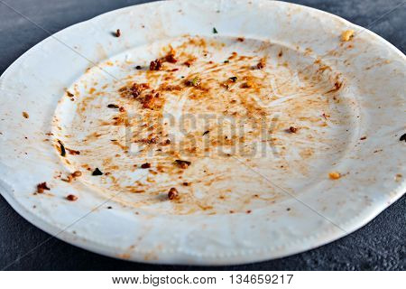 White dirty plate after spaghetti pasta with meat and tomato sauce. Red sauce spots on dish area. Stone background