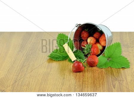 Strawberry is scattered out of the bucket. strawberries with leaves in basket on wooden table / Isolated on white background without shadows /. Natural product from our own garden.