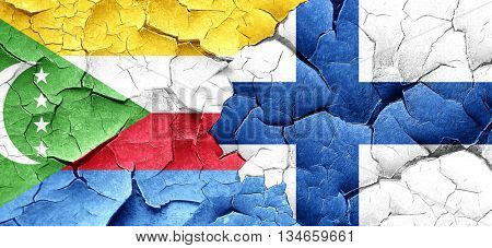 Comoros flag with Finland flag on a grunge cracked wall