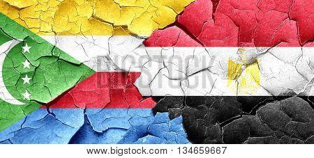 Comoros flag with egypt flag on a grunge cracked wall
