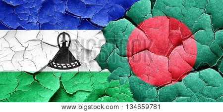 Lesotho flag with Bangladesh flag on a grunge cracked wall