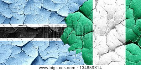 Botswana flag with Nigeria flag on a grunge cracked wall