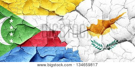 Comoros flag with Cyprus flag on a grunge cracked wall