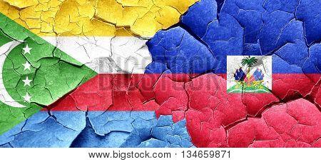 Comoros flag with Haiti flag on a grunge cracked wall