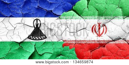 Lesotho flag with Iran flag on a grunge cracked wall