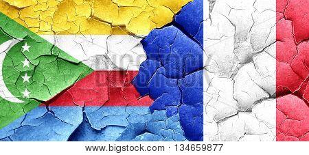 Comoros flag with France flag on a grunge cracked wall