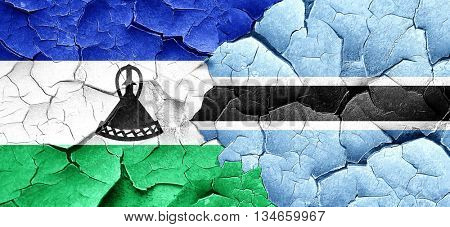 Lesotho flag with Botswana flag on a grunge cracked wall
