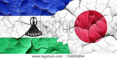 Lesotho flag with Japan flag on a grunge cracked wall