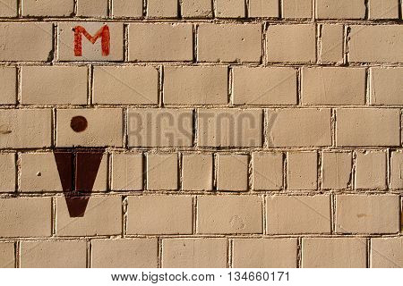 Male toilet sign on the brick wall