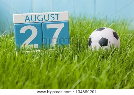 August 27th. Image of august 27 wooden color calendar on green grass lawn background with soccer ball. Summer day. Empty space for text.